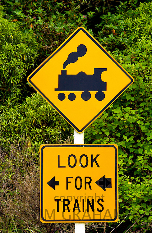 Road traffic sign 'look  for trains' on railway crossing, North Island, New Zealand