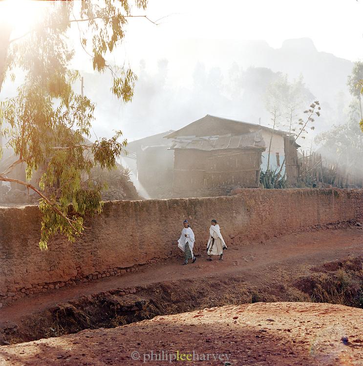 Two Women Walking Along The Wall Of Lalibela Village, Ethiopia.