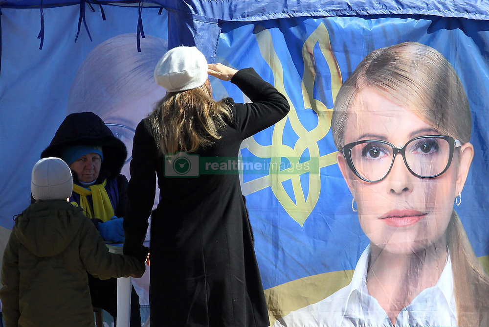 March 28, 2019 - Kiev, Ukraine - A woman salutes as she passes by a pre-election tent of presidential candidate Yulia Tymoshenko, in central Kiev, Ukraine. The presidential elections will take place in Ukraine on 31 March 2019. (Credit Image: © Serg Glovny/ZUMA Wire)