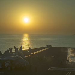 USS John C Stennis CVN-74 Aircraft Carrier.Pic Shows Flight and Deck personnel prepare F-18 Super Hornets for take off as the sun sets