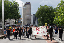 """© Licensed to London News Pictures; 03/07/2021; Bristol, UK. Kill the Bill protesters carry a banner saying """"Priti Shit New Law"""" in reference to the Home Secretary Priti Patel and the Police, Crime, Sentencing and Courts Bill during a fourteenth """"Kill the Bill"""" protest in Bristol against the Police, Crime, Sentencing and Courts Bill during the Covid-19 coronavirus pandemic in England. Protesters marched up the M32 and blocked traffic for a time. The Police, Crime, Sentencing and Courts Bill proposes new restrictions on protests and is due to return to the House of Commons for debate on Monday 05 July. Some previous Kill the Bill protests in Bristol had violence. Photo credit: Simon Chapman/LNP."""