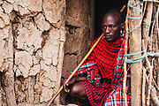 A Moran warrior of the Maasai tribe sitting in the doorway of a hut in his village ,Amboseli, Kenya, Africa