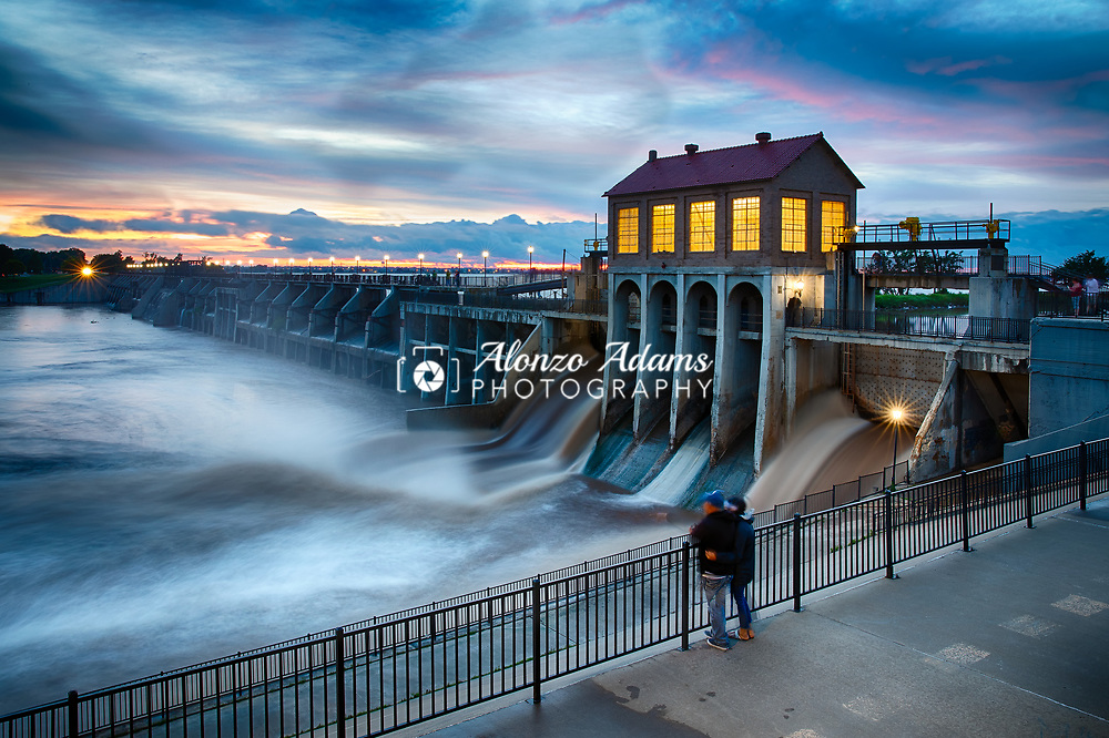 The Overholser Dam releases flood water from the North Canadian River adjacent to Lake Overholser in Oklahoma City at dusk on Thursday, June 6, 2019. Photo copyright © 2019 Alonzo J. Adams.