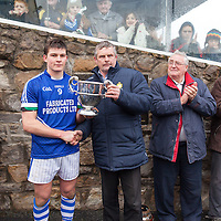 Cratloe's Captain Liam Markham receives the winning Clare Cup from Cllr. Joe Cooney, Clare GAA Vice Chairman