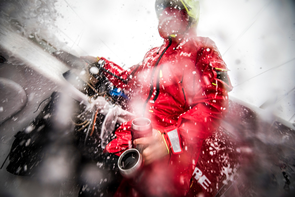 Leg 02, Lisbon to Cape Town, day 17, on board MAPFRE, ''It is a short way to the workplace but it is a wet and cold one'' Antonio Cuervas-Mons going out from the hatch for his watch carring a lot of coffee for everyone. Photo by Ugo Fonolla/Volvo Ocean Race. 21 November, 2017