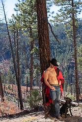 shirtless cowboy with his dog in the woods