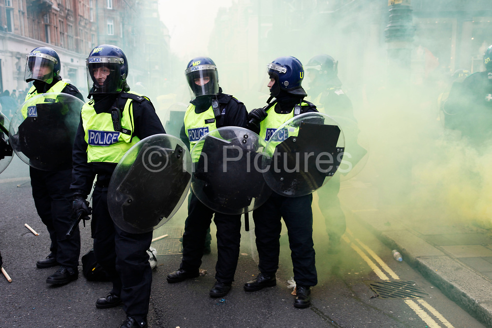 Riot police surrounded by yellow smoke from a smoke bomb stand their ground after a clash on a street in Mayfair. Anti capitalists / anarchists go on the rampage through central London on the back of the peaceful TUC protest march. The masked demonstrators ran a twisting route through the capital confusing the police and creating a situation which was very difficult to manage. The protesters attacked banks, shops and hotels, and the police in riot gear fought  face to face with them as they were pelted with ammonia, paint and fireworks loaded with coins.