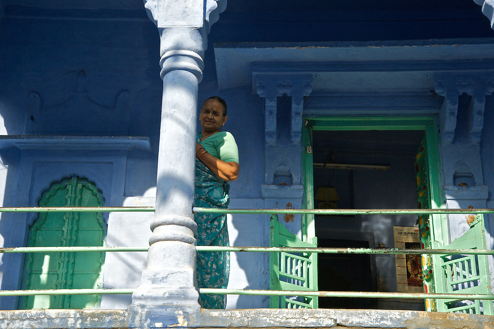 """Johpur is known as """"The Blue City"""" due to the Brahman neighborhoods being painted in blue.  The blue is an historic color for Brahman homes that most of the city adopted.  It is said to keep the mosquitoes at bay and the temperatures cooler.  Many of the doors are also painted green and when this women appeared wearing green she seemed just perfect for this scene."""