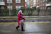 Elderly woman out with her shopping bag wearing her pink coat and headscarf walking through a housing estate in the City of London, England, United Kingdom.