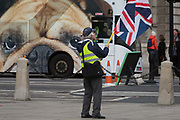 A far-right yellow vest protests as a British Bulldog bus ad drives through Parliament Square opposite the UK Parliament in a week that Prime Minister Theresa May once again asks for MPs to back her Brexit deal, on 14th January 2019, in Westminster, London, England.