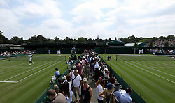 A general view of spectators watching the match action on courts 5 and 6 on day three of the Wimbledon Championships at the All England Lawn Tennis and Croquet Club, Wimbledon.