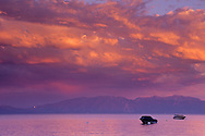 Sunset light on storm clouds over boats anchored in Lake Tahoe, California