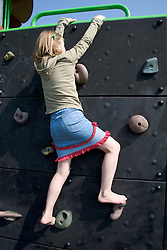 Young girl climbing on a climbing wall in the local playground,