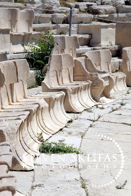 Athens. Greece. View at the Theatre of Dionysos of the first row seats which were reserved for priests, dignitaries and official. Some seats have inscriptions for the person it was reserved. The Theatre was originally established in the 6th century BC and enlarged and improved over the Classical, Hellenistic and Roman periods and was the first theatre built of stone. The famous tragedies of Aeschylus, Sophocles and Euripides and the comedies of Aristophanes were first performed here in the 5th century BC. What is seen today is largely from the 4th century BC during the time of Lycurgus, who controlled public investment in Athens from 338 to 324 BC. The structure has 25 surviving tiers of seats from the original 65 and had a capacity to seat 17,000 spectators. The Stage front is Roman and is represented by the Bema of Phaedrus, which has 2nd century AD decorative reliefs showing scenes in the life of Dionysus, god of wine and patron god of the Greek stage.