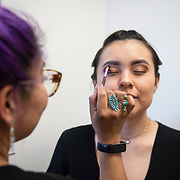 April Tucker sits for makeup artist Goldie Tom before a Gallup fashion show featuring designers ACONAV and JG Indie Saturday, June 22 at the Downtown Conference Center in Gallup.