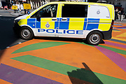 Police van with blue and yellow livery passes over the new graphic and patterned multi-coloured pedestrian crossings at Piccadilly Circus on 10th August 2021 in London, United Kingdom.