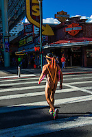 Nearly naked man (wearing a thong) walking on Fremont Street, Downtown Las Vegas, Nevada USA.