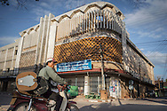 A motorbike pass by an art deco cinema in Savannakhet, Laos, Southeast Asia
