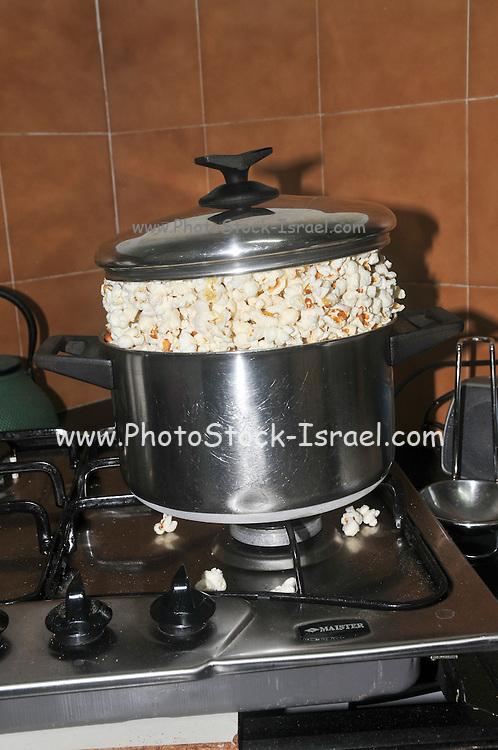 A pot of pop corn on a gas stove
