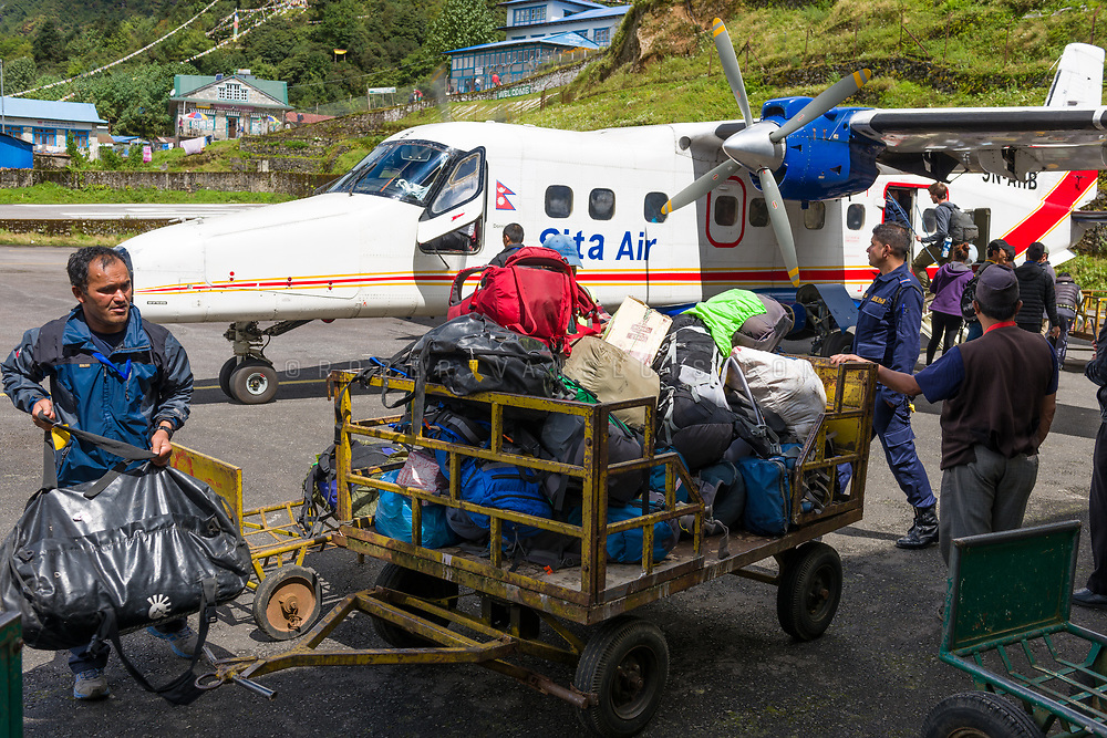Unloading luggage from a plane at Tenzing Hillary Airport, Lukla, Nepal. Photo © robertvansluis.com