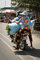 A woman holds on to a large sack while riding on the back of a moped in Phnom Penh, Cambodia