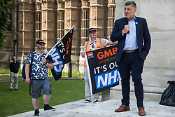 London, UK. 20th July, 2021. Ian Byrne, Labour MP for Liverpool West Derby, addresses NHS workers from the grassroots NHSPay15 campaign outside Parliament before a march to 10 Downing Street to deliver a petition signed by over 800,000 people calling for a 15% pay rise for NHS workers. At the time of presentation of the petition, the government was believed to be preparing to offer NHS workers a 3% pay rise in 'recognition of the unique impact of the pandemic on the NHS'.