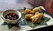 Vietnamese Spring Rolls served with soy and chili peppers. Dark Chop sticks on white plate.