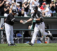 CHICAGO - JUNE 27:  Paul Konerko #14 celebrates with third base coach Jeff Cox #6 of the Chicago White Sox after Konerko hit his 20th home run of the season against the Chicago Cubs on June 27, 2010 at U.S. Cellular Field in Chicago, Illinois.  The Cubs defeated the White Sox 8-6.  (Photo by Ron Vesely)