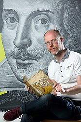 © Licensed to London News Pictures. 21/4/2016. Birmingham, UK. Rare and unseen Shakespeare items, including the first Folio are to go on display in a free exhibition at Birmingham Library from tomorrow. Pictured, Shakespeare Curator Julian Harrison with one of the items in the exhibition. Photo credit : Dave Warren/LNP