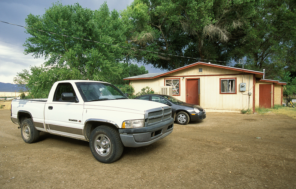 Cars parked outside a family home on the San Carlos Apache Indian Reservation in Arizona, USA. June 2004.