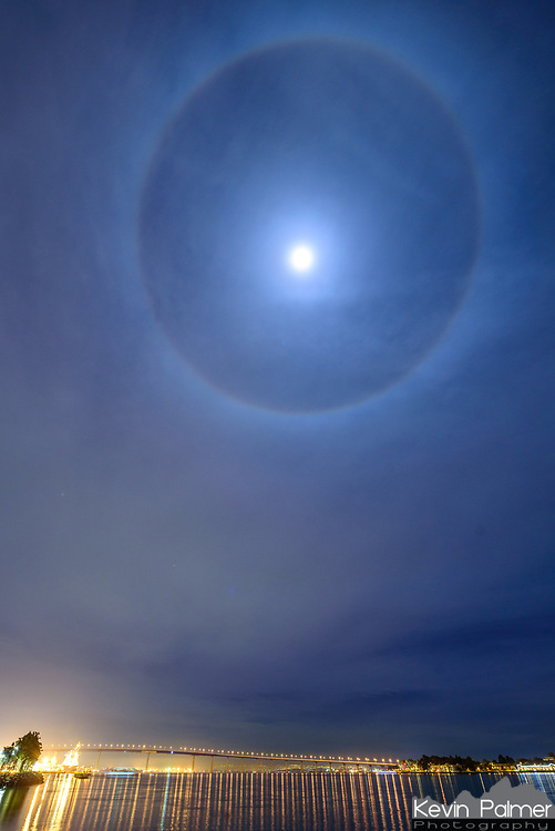 This bright and obvious halo appeared around the nearly full moon in San Diego. The lights at the bottom are from the Coronado Bridge.