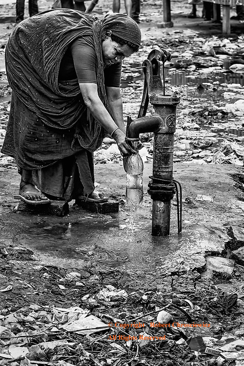 Clean Water  (B&W): A lady risks the garbage and filth to use a manual water pump and fill a container with water, Mymensingh Bangladesh.