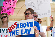 Protestors stand in front of the Collin County Courthouse calling for action to be taken against Texas Attorney General Ken Paxton on August 3, 2015. (Cooper Neill for The Texas Tribune)