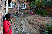 After school Masindi (9 years old) and Tlhase (3 years old) play in the garden.