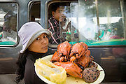 26 JUNE 2006 - CENTRAL CAMBODIA: A woman sells snacks to bus passengers at a rest stop on Highway 6 between Phnom Penh and Siem Reap, Cambodia. PHOTO BY JACK KURTZ