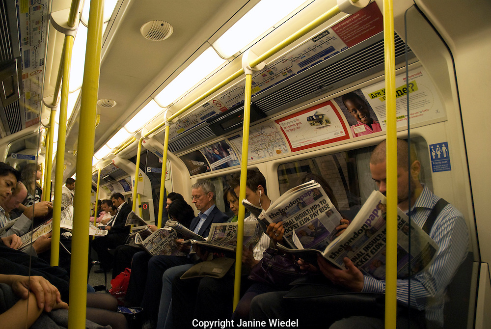 Commutors reading newspapers on the tube train on the way home