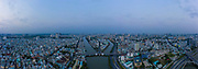 Symmetrical early morning drone panorama before sunrise featuring 3 direction bridge over canal. The big sprawling city is waking up.