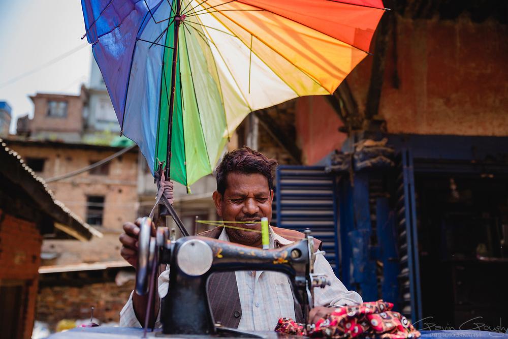 A man using a sewing machine in the street beneath a broken rainbow-coloured umbrella, Chandra Man Singh Maskey Marg, Kathmandu Metropolitan City, Nepal