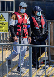 © Licensed to London News Pictures. 20/07/2021. Dover, UK. A migrant is escorted by a Border Force officer as he is brought ashore at Dover Harbour in Kent after crossing the English Channel. It is being reported that at least 430 migrants crossed the English Channel to the UK on Monday, a new single day record. Photo credit: Stuart Brock/LNP