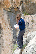 Israel, Carmel Mountain, Nahal Mearot (Cave River) nature reserve A female traveller checking hee guide book at the edge of a cliff while admiring the view. Model Release available