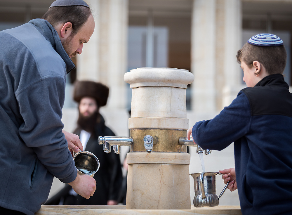 19 April 2019, Jerusalem: A man and a young boy wash their hands, as on the first day of Pesach (Passover) Jews gather to pray by the Western Wall in Jerusalem, considered as the most sacred and holy place for the Jews.