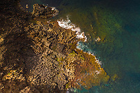 Aerial view of waves breaking on a coast with rock formation, Spain.