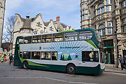 Electric hybrid green number bus drives along a street in Oxford City, England, United Kingdom.  Stagecoach hybrid buses are more environmentally greener than traditional buses using 30% fuel and third less CO2 emissions, the buses are also much quieter.
