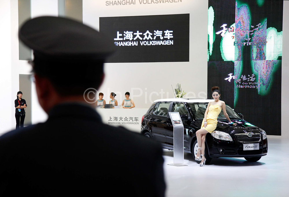A guard stands near a Shanghai Volkswagen display at the Auto Shanghai 2009 in Shanghai, China, on Monday, April 20, 2009. Automakers from across the world are increasingly focusing their efforts on China, the largest auto market in the world and the only major market with prospects of high growth rate.