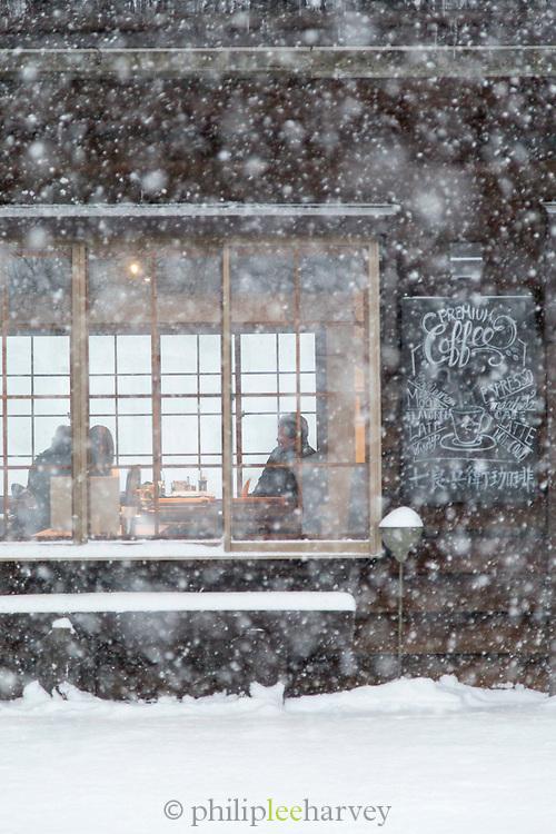 People sitting inside cafeteria during snowy day, Nozawaonsen, Japan