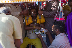 © Licensed to London News Pictures. 03/02/2015. Ipoh, Malaysia. A devotee with metal sticks pieced through his mouth carrying a kavadi takes a rest while waiting to enter Kallumalai Murugan Temple in Ipoh, Malaysia, during the Thaipusam Festival,  Tuesday, Feb. 3, 2015. Photo credit : Sang Tan/LNP