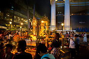 Worshipers in the Erawan Shrine, Bangkok. It is Brahman, not strictly Buddhist. And yet, this famous shrine attracts more visitors than many of the city's temples. It was erected during the mid 1950s, after the Thai government had decided to build the luxury Erawan Hotel on this location. However, the first stages of the construction were beset with so many problems that superstitious labourers refused to continue unless the land spirits were appeased. Thailand.