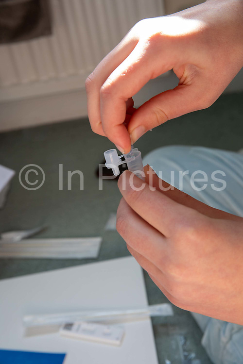 A secondary school pupil sits on the floor in her room and prepares herself to do a COVID-19 Lateral Flow test. Lateral Flow Device LFD kits were given to all secondary school pupils in England so they can test themselves twice a week at home on the 21st March 2021 in Folkestone, United Kingdom.