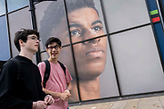 Two young man walk beneath the large billboard, a portrait of English football player, Marcus Rashford, outside the Strand branch of Coutts Bank, on 14th October, 2021, in Westminster, London, England. Marcus Rashford has recently been awarded an honourary degree by The University of Manchester in recognition of his political campaigning on behalf of the underprivilged in particular, of school meals and his philanthropy. He currently plays for Manchester United and is in the English national team. He has also been the victim of online racial abuse.