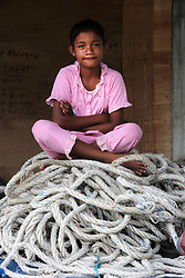 Portrait of T Bukhari and Zhuhra's daughter (unnamed) sitting on fishing boat ropes in Lhok seudu Village port. Oxfam had built shelter following the Indian Ocean Tsunami of Dec 2004, District Aceh Besar, Aceh Province, Sumatra, Indonesia